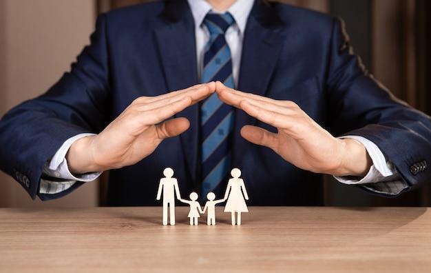 Un homme en costume tient la main sous la forme d'une maison sur la famille. concept d'assurance.