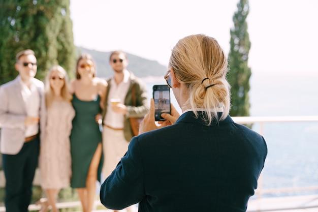Un homme en costume tire sur un groupe de personnes sur un smartphone sur fond de mer