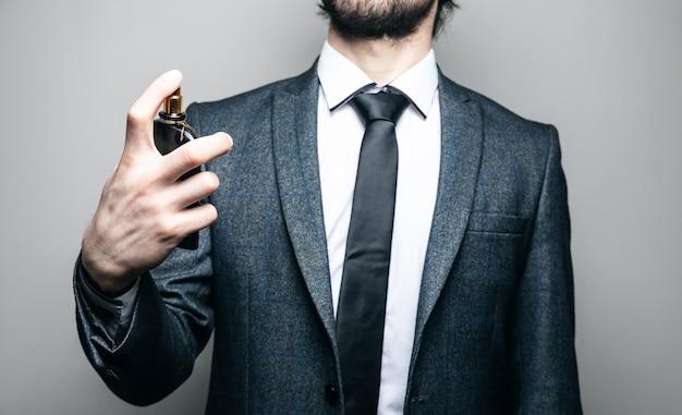 Homme en costume et verres saupoudre de parfum sur un mur gris