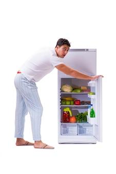 Homme à côté du frigo rempli de nourriture