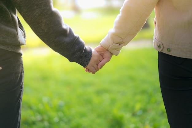 Un homme à côté d'une femme, un gars et une fille sont debout, se touchent, se tenant par la main