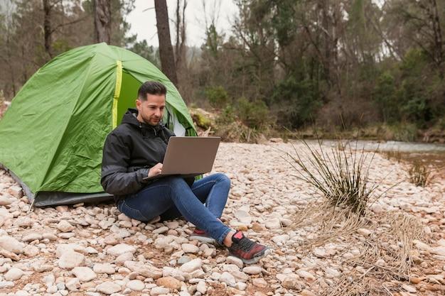 Homme à côté de la tente avec ordinateur portable