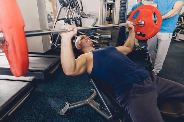 Homme couché sur un banc de faire une séance d'entraînement avec une barre.