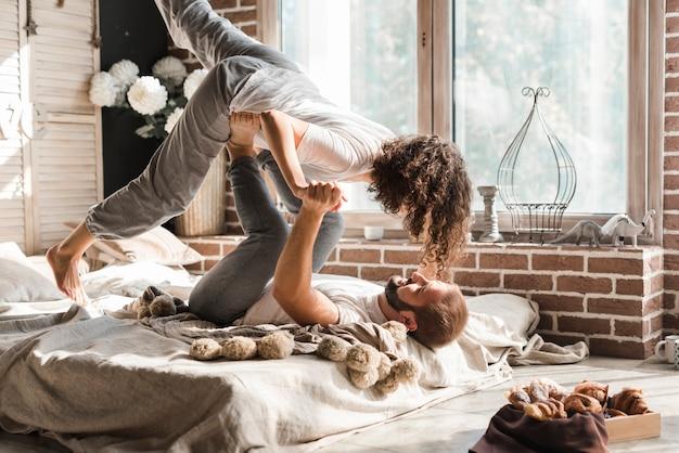 Homme couché sur le lit, portant sa petite amie sur ses pieds
