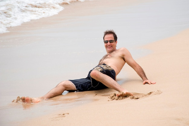 Homme couché sur le sable le long du rivage à bali