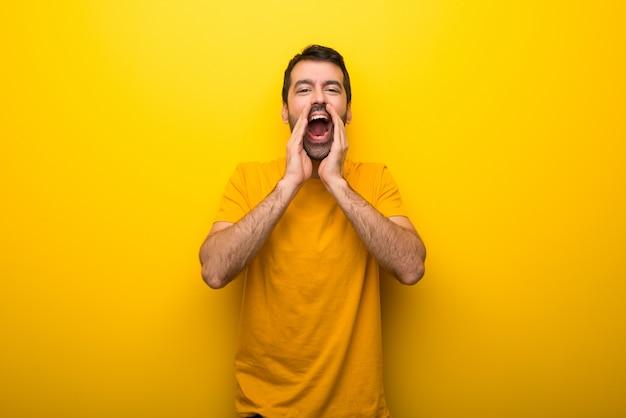 Homme de couleur jaune vibrant isolée criant et annonçant quelque chose