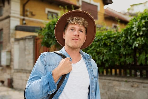 Homme de coup moyen avec un chapeau voyageant