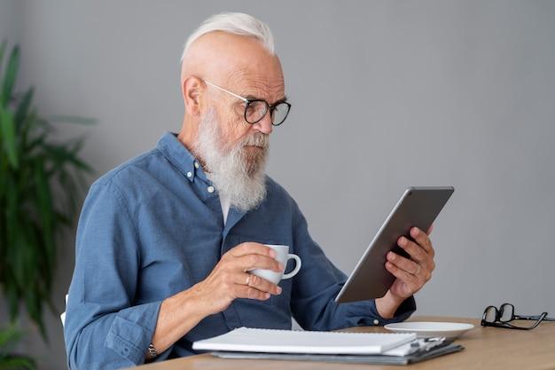 Homme de coup moyen étudiant au bureau avec tablette