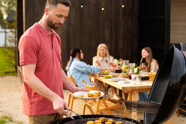 Homme de coup moyen faisant un barbecue