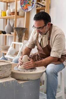 Homme de coup moyen faisant de la poterie à l'intérieur