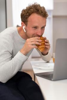 Homme de coup moyen mangeant un croissant
