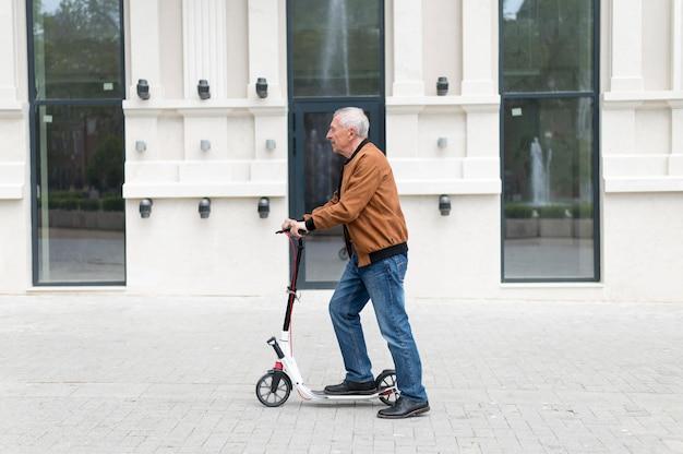 Homme de coup moyen avec scooter