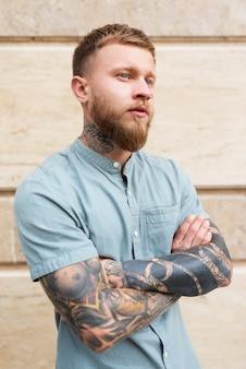 Homme de coup moyen avec des tatouages à l'extérieur