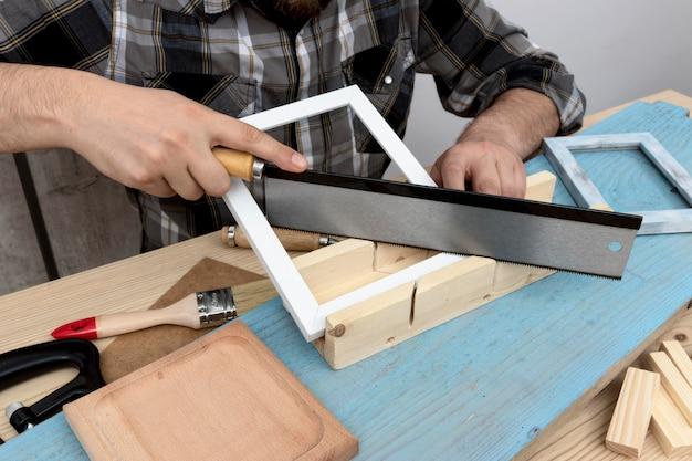 Homme coupant le concept d'atelier de menuiserie en bois