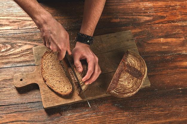Homme coupant du pain fraîchement cuit sur une vieille planche en bois à plat