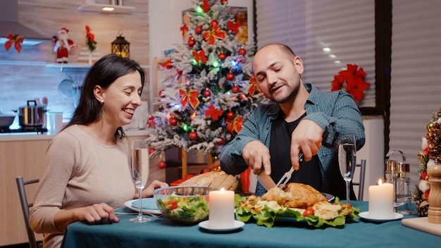 Homme coupant du poulet pour une femme au dîner de fête la veille de noël