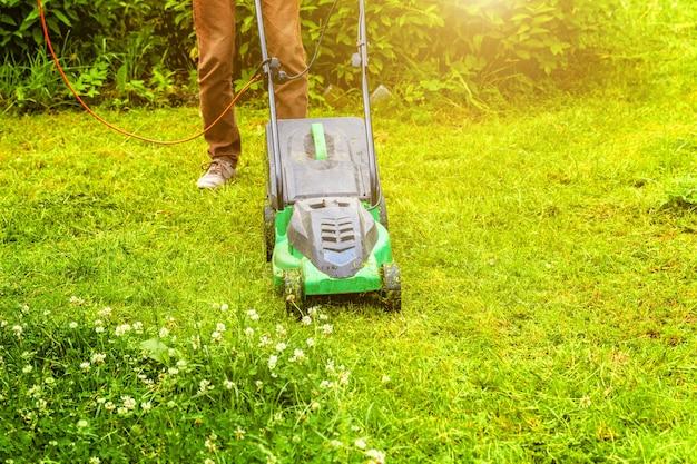 Homme coupant l'herbe verte avec la tondeuse à gazon dans la cour