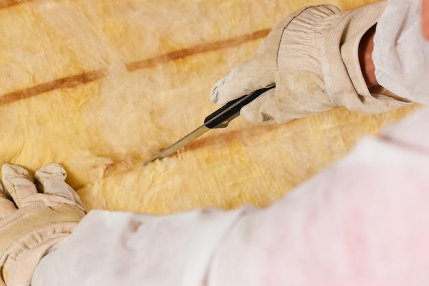 Homme coupant un matériau isolant pour le bâtiment