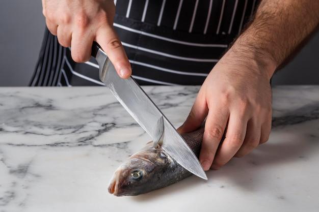 Homme coupant un poisson de basse pour la cuisine