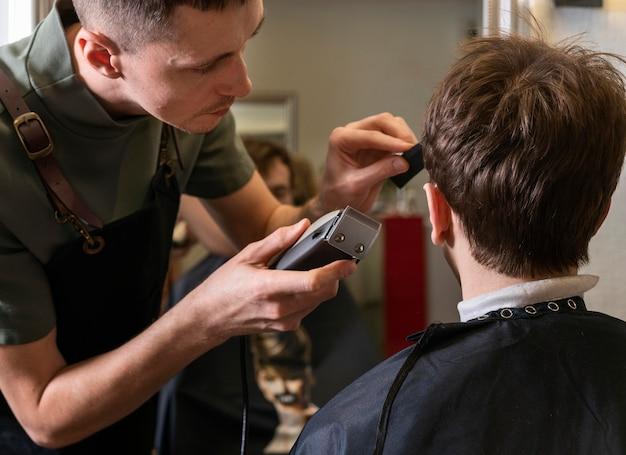 L'homme coupe les cheveux d'un client