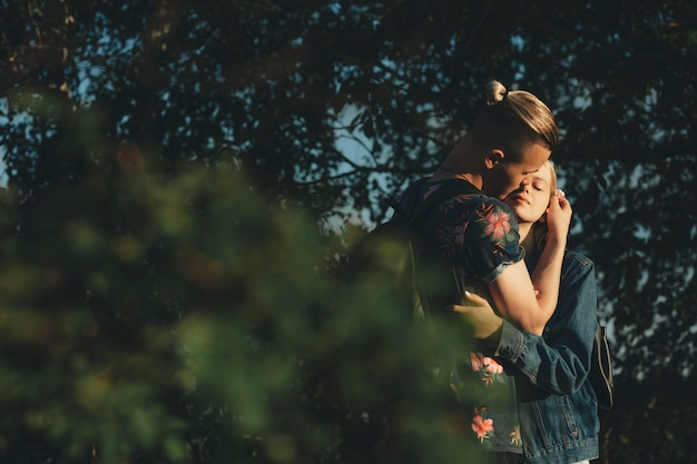 Homme avec coupe de cheveux créative embrassant jeune femme séduisante aux yeux fermés debout ensemble à l'extérieur au coucher du soleil avec des feuilles vertes sur le premier plan flou