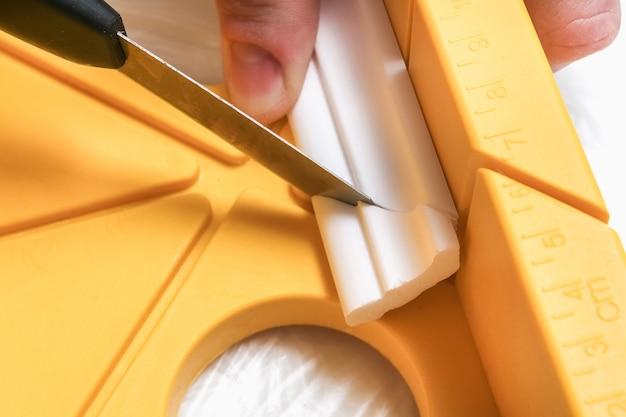 L'homme coupe la corniche de moulage sur la boîte à onglets.