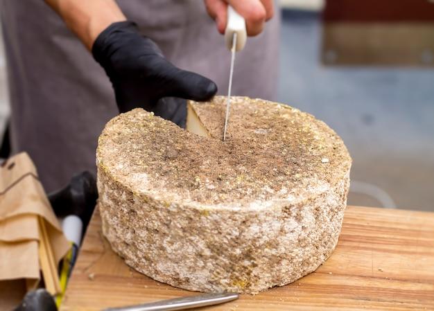 Un homme coupe du fromage.