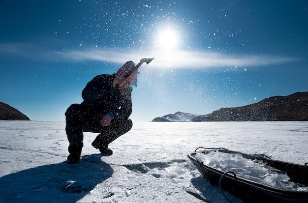 Un homme coupe la glace avec une hache sur le lac gelé du baïkal en hiver