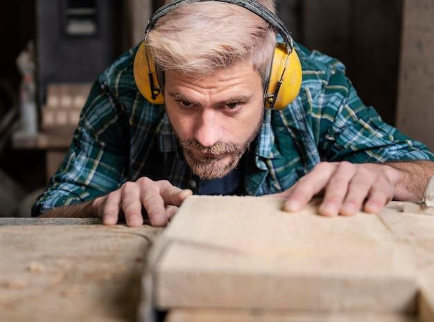 L'homme coupe des planches de bois