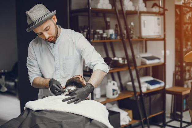 L'homme coupe sa barbe dans le salon de coiffure.