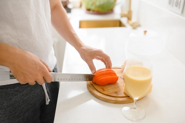 Un homme coupe les tomates sur une planche à découper dans une cuisine lumineuse.