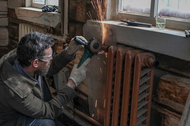Un homme coupe de vieux radiateurs dans sa maison en bois avec une meuleuse d'angle et un disque de coupe