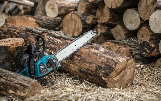 Homme couper du bois avec une tronçonneuse