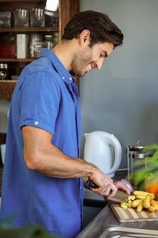 Homme, couper les légumes au comptoir de la cuisine