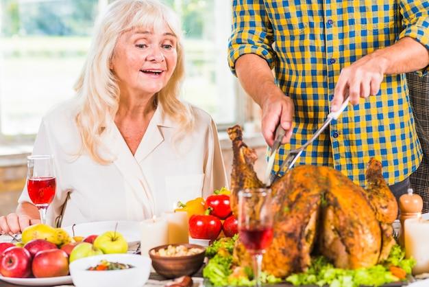 Homme, couper, poulet rôti, à, table, près, femme surprise