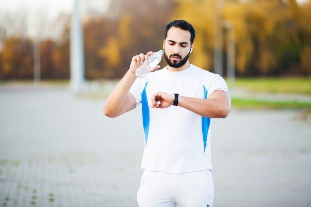 Homme coureur épuisé boire de l'eau sur le parc après l'entraînement
