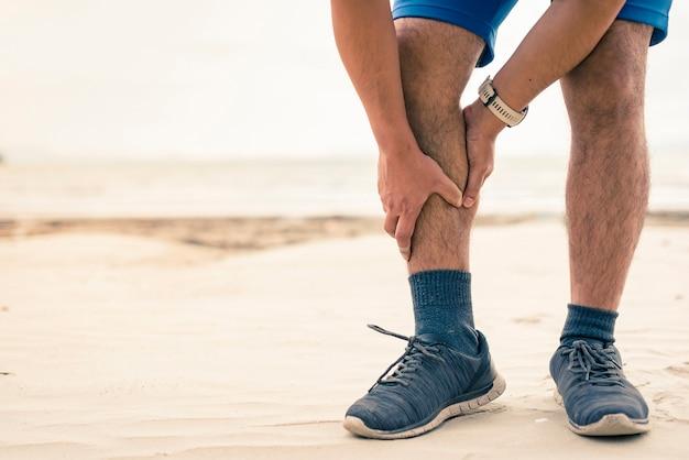 Homme coureur tenir sa jambe blessée sportive sur le fond de la plage
