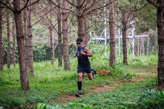 Un homme coureur de trail et pieds d'athlète portant des chaussures de sport pour le trail running en forêt