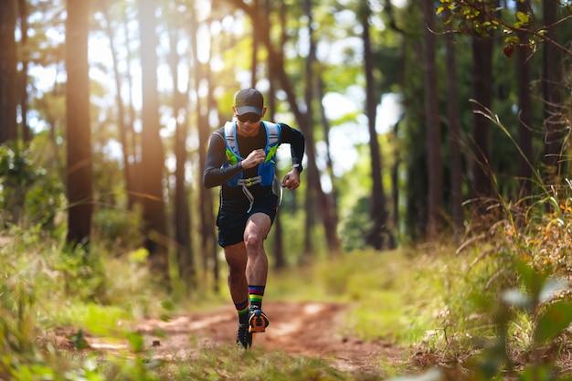 Un homme coureur de trail. et pieds d'athlètes portant des chaussures de sport pour le trail running en forêt