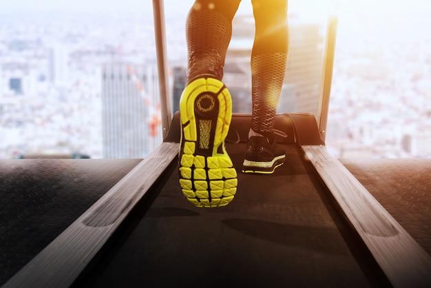 Homme courir avec tapis roulant à la salle de sport dans une journée ensoleillée