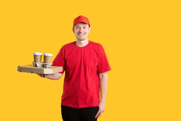 Homme de courrier en bonnet rouge et t-shirt détient des boîtes et du café sur jaune