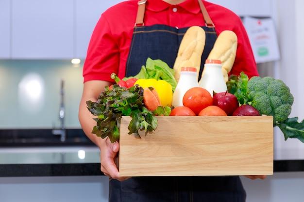 Homme de courrier de livraison d'épicerie en uniforme rouge avec boîte d'épicerie avec fruits et légumes frais