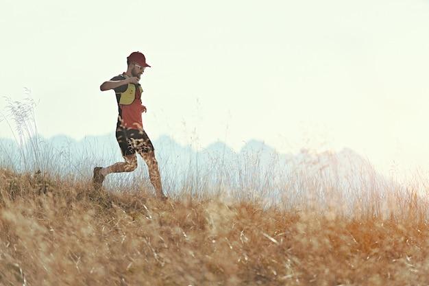 L'homme court en descente parmi les prairies de montagne d'automne