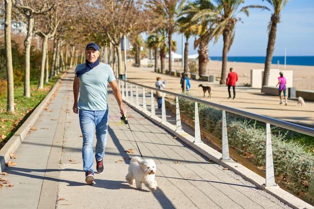 L'homme court avec son chien dans le parc.