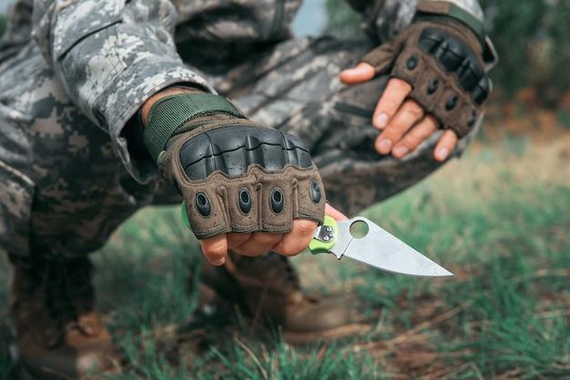 Un homme avec un couteau dans la forêt.