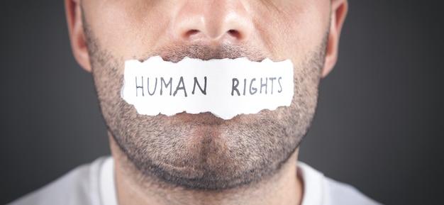 Homme couvrant sa bouche avec un texte des droits de l'homme sur du papier déchiré.