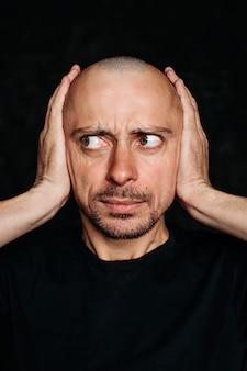 Homme couvrant ses oreilles avec ses mains
