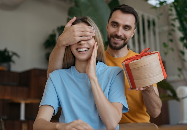 Homme couvrant ses yeux de petite amie, donnant une boîte cadeau. beau couple assis ensemble dans un café, date romane