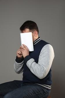 Homme couvrant le visage avec un livre en lisant sur un mur gris. célébrer, éduquer, art, profiter du nouveau concept de personnages.