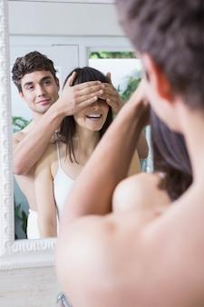 Homme couvrant les yeux de la femme debout devant le miroir